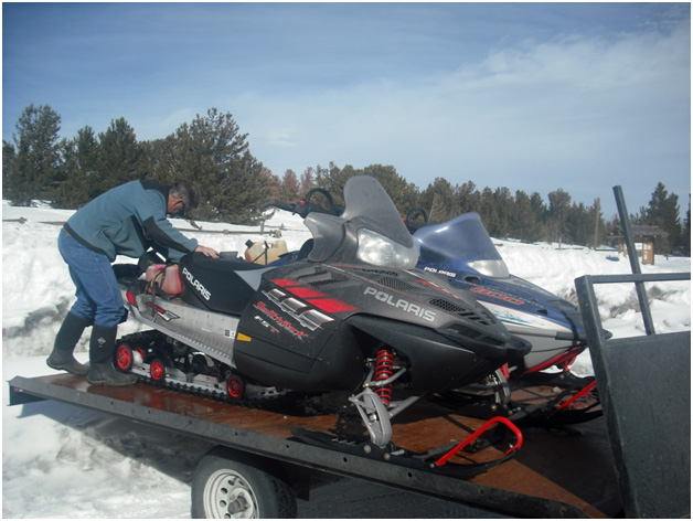 RealRanchers Jim and Timmery Hellyer from Lander, Wyo. take a break from feeding their beef cattle to snowmobile.