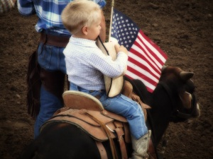 Young cowboy riding miniature bull at the Wyoming State Fair during Star Spangled Banner