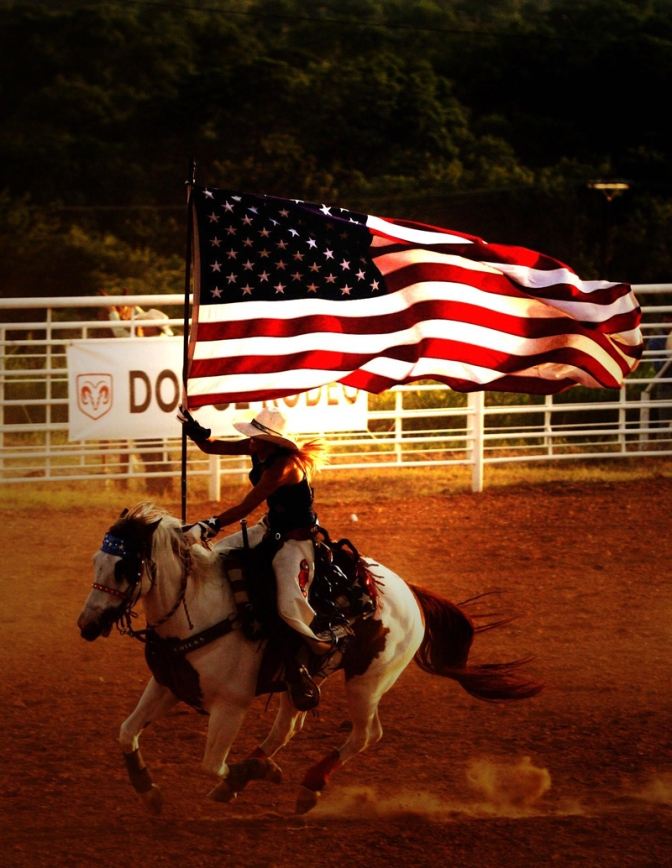 Rodeo Queen carries flag on horse