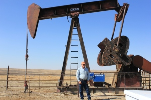 Doug Cooper stands infront of an oil well