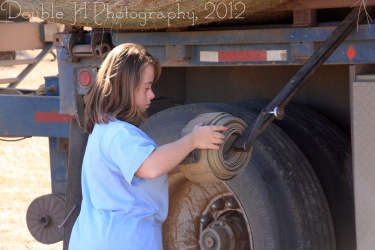 RealRancher Holly Hamilton helps wind straps from a semi-truck load of hay on her family ranch near Lance Creek, Wyo.
