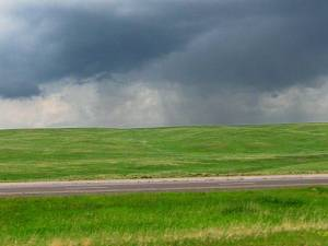 Green prairie and storm
